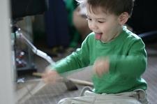 Ett litet barn som lirar trummor