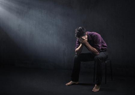 Deprimerad man i ett mörkt rum